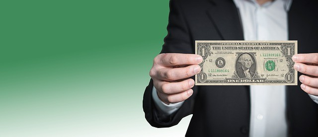 Man holding 1 dollar bill