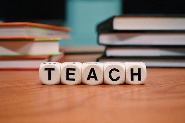 """Word """"TEACH"""" written with scrabble cubes"""